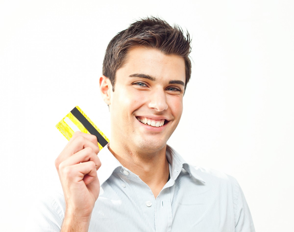 young-man-happy-holding-credit-card-e1427080761843.jpg